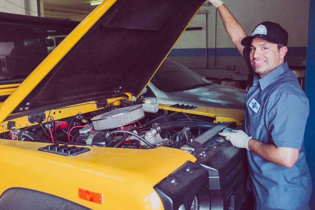 Mecânico em frente a um carro amarelo com o capo aberto e o motor exposto
